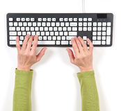 Hands in green jacket and grey keyboard Royalty Free Stock Photography