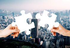 Hands with green puzzle over city background Stock Photography