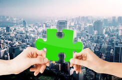 Hands with green puzzle over city background Royalty Free Stock Photography