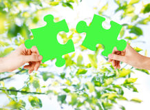 Hands with green puzzle over natural background Stock Photography