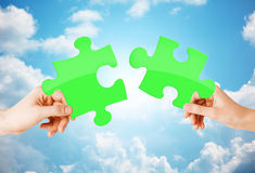 Hands with green puzzle over sky background Royalty Free Stock Photos