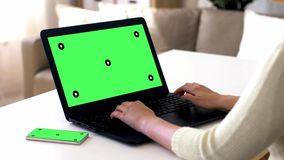 Hands with green screen on laptop and smartphone. Technology concept - female hands typing on laptop with green screen and smartphone on table stock video
