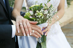 Hands of the groom and the bride. With wedding rings against a bouquet Stock Photography