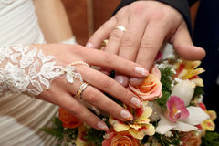 Hands of the groom and the bride on background of wedding bouque Royalty Free Stock Photos
