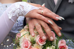 Hands of the groom and the bride on background of wedding bouque Stock Photo