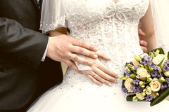 Hands of  groom and  bride close-up and bridal bouquet Stock Photography