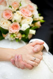 Hands of groom and bride with engagement ring and wedding bouquet. Of pale pink and white flowers Stock Photo