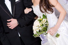 Hands of a groom and a bride with a flower bouquet Stock Photos