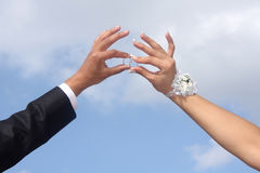 Hands of  groom and  bride hold wedding rings. Against  blue sky Stock Images