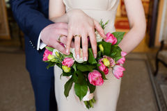 Hands of the groom and bride with rings and wedding bouquet Stock Photography