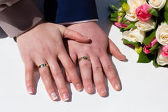 Hands of the groom and bride with rings and wedding bouquet Royalty Free Stock Images