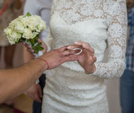 Hands of the groom and bride is wearing a ring on the finger on the day of the wedding ceremony. Stock Photography