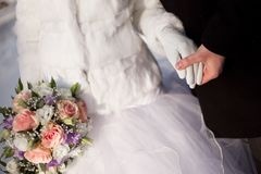 Hands of groom and bride with wedding bouquet Royalty Free Stock Image