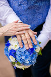 Hands of groom and bride on a wedding bouquet Stock Photography