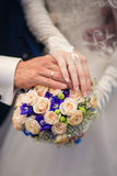 Hands of groom and bride on a wedding bouquet Stock Images