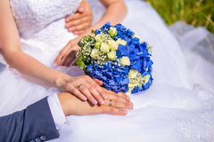 Hands of groom and bride on a wedding bouquet Stock Photo
