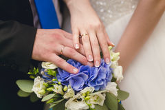 Hands of groom and bride on a wedding bouquet Stock Photos