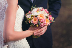 Hands of groom and bride on a wedding bouquet Royalty Free Stock Images