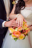 Hands of groom and bride on a wedding bouquet Royalty Free Stock Photos
