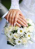 Hands of the groom and the bride with wedding rings and a weddin Stock Photos