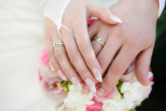 Hands of the groom and the bride with wedding rings and a wedding bouquet Royalty Free Stock Images
