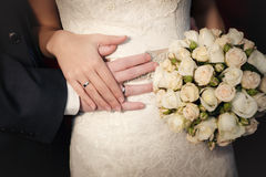 Hands of the groom and the bride with wedding rings and a wedding bouquet Stock Photography