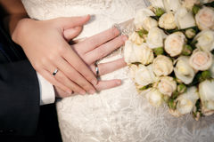 Hands of the groom and the bride with wedding rings and a wedding bouquet Stock Image