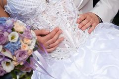 Hands of groom gently embracing brides's waist Royalty Free Stock Image