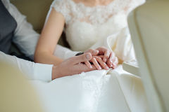 Hands of the groom touch the fingers of the bride, her palms in Royalty Free Stock Photo