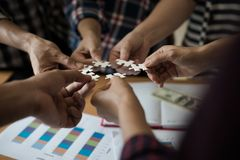 Hands group of business people assembling jigsaw puzzle white. B stock image