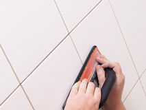 Hands grouting a ceramic tile. Floor or wall using a rubber float Royalty Free Stock Photos