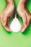 Hands guarding energy saving eco lamp close up.  stock photo
