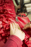 Hands Guiding Red Cloth Through Sewing Machine Royalty Free Stock Image