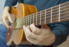 The composer composes a melody or a song on the gu. The man playing the guitar in the frame arms, and musical instrument Stock Photography