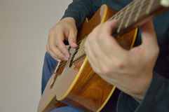 Hands and guitar - a man plays an instrument in a. The man playing the guitar in the frame arms, and musical instrument Royalty Free Stock Photos