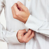 Hands a guy fastened the buttons on sleeve bright shirt closeup Stock Images