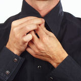 Hands a guy fastened collar of black shirt closeup Royalty Free Stock Photo