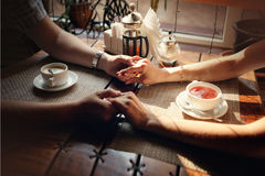 Hands of the guy and hand of the girl at a table with a cup of tea and a cup of coffee Royalty Free Stock Photography