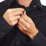 Hands a guy unbutton his black shirt closeup Royalty Free Stock Images