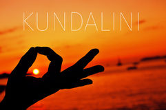 Hands in gyan mudra and text kundalini. Closeup of a young man meditating with his hands in gyan mudra at sunset and the text kundalini royalty free stock photo