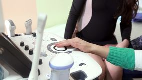 Hands of the gynecologist for the operation of the ultrasonic device. Doctor hands with ultrasound equipment operation of the ultrasonic device Prenatal testing stock footage