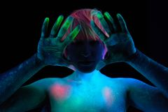 Hands and hair of a girl model painted with neon colored paints in the light of ultraviolet lamps. stock photos