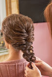Hands of hairdresser plaiting braid. Female hairdo back view. Braid designs for women Royalty Free Stock Images