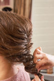 Hands of hairstyist plaiting braid. Female hairdo macro Stock Images