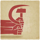 Hands with hammer and sickle old background Stock Image