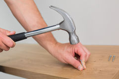 Hands hammering nail in wooden bench Stock Image