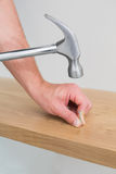 Hands hammering nail in wooden bench Stock Images