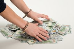 Hands handcuffed over a bunch of dollars, over white background stock photo