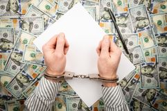 Hands in handcuffs on background of sheet of paper and dollars. top view stock image