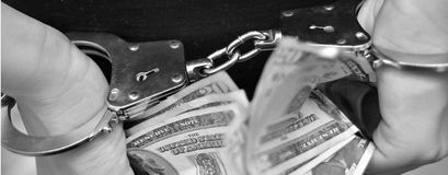 Hands with handcuffs holding dollars. Bills Stock Photography